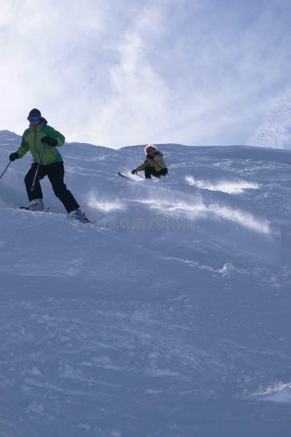 Esquiadores amarelos na neve do pó fotos de stock