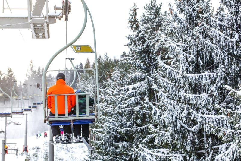 Esquiadores no elevador de cadeira, pista abaixo, árvores cobertos de neve no lado direito imagem de stock royalty free