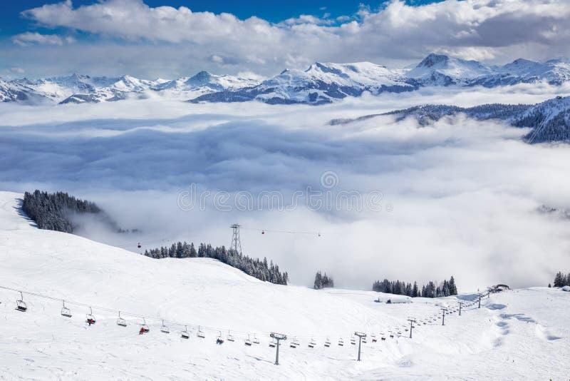 Esquiadores no elevador de esqui que apreciam a vista aos cumes nevoentos em Áustria e no país nevado bonito fotos de stock