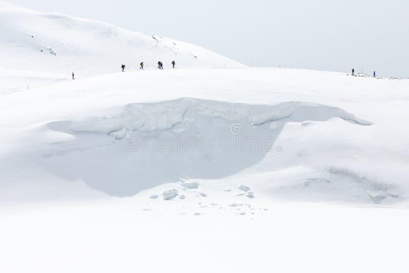 Esquiadores que andam em cordilheiras cobertos de neve fotografia de stock