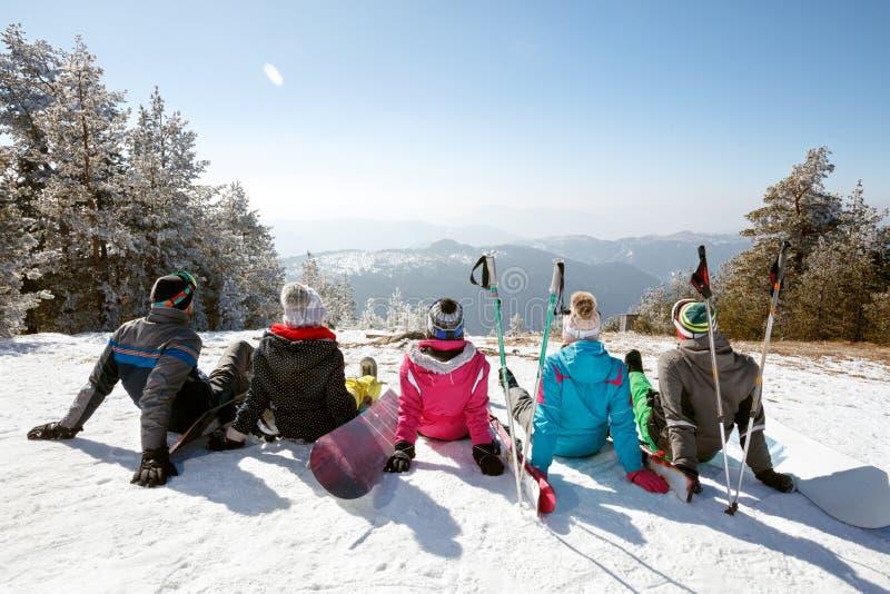 Esquiadores que descansan sobre nieve del esquí, opinión de la parte posterior imagen de archivo