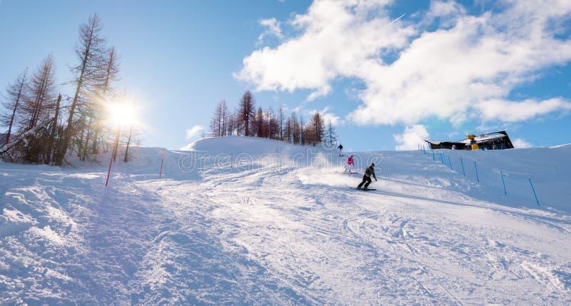 Esquiadores que esquían cuesta abajo en paisaje soleado de la montaña foto de archivo libre de regalías