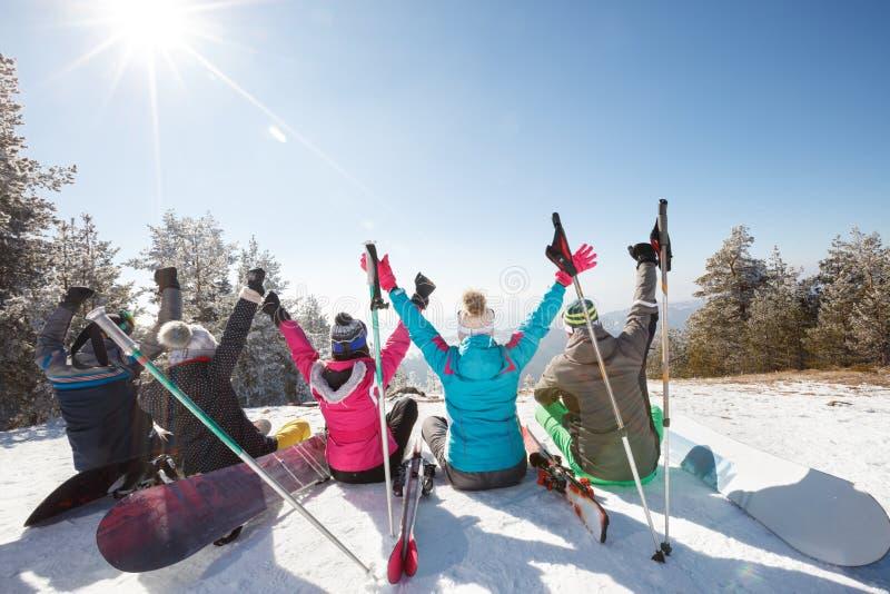 Esquiadores que se sientan en nieve con las manos para arriba y que descansan, visión trasera imagen de archivo libre de regalías
