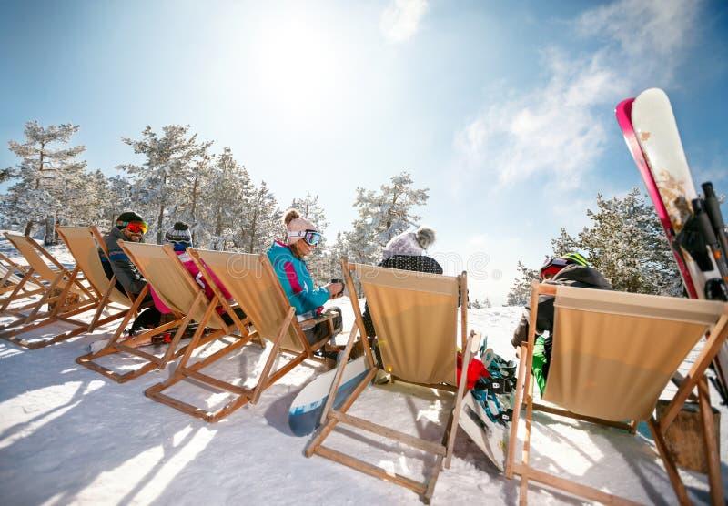 Esquiadores que sentam-se com as cadeiras de plataforma em montanhas do inverno Vista traseira imagem de stock royalty free
