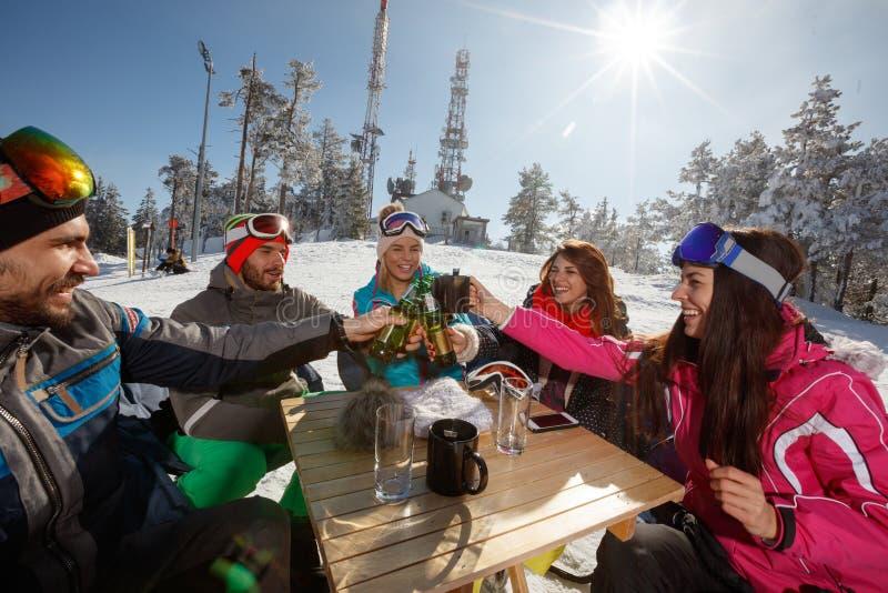 Esquiadores que tuestan con las botellas de cerveza fotografía de archivo