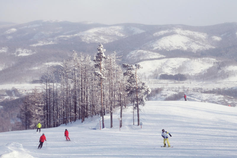 Esquiadores y snowboarders en las montañas de Urales imagen de archivo