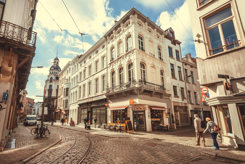 Esquina brillante de calles en ciudad histórica con las piedras cobbled, los restaurantes y los mayores que caminan imágenes de archivo libres de regalías