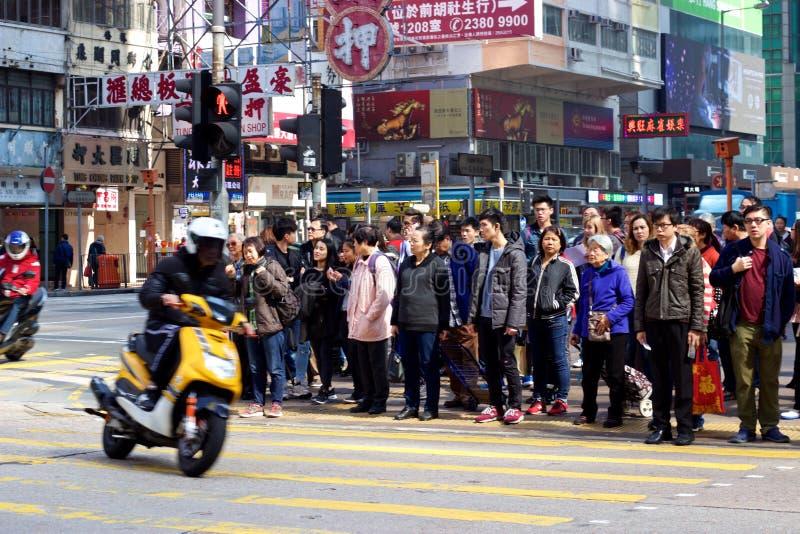 Esquina de calle de Mong Kok: Vueltas de la moto, espera de los peatones a la cruz foto de archivo libre de regalías