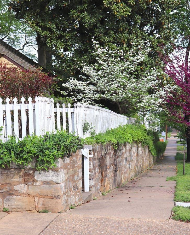 Esquina de calle, naturaleza y valla de estacas blanca foto de archivo libre de regalías