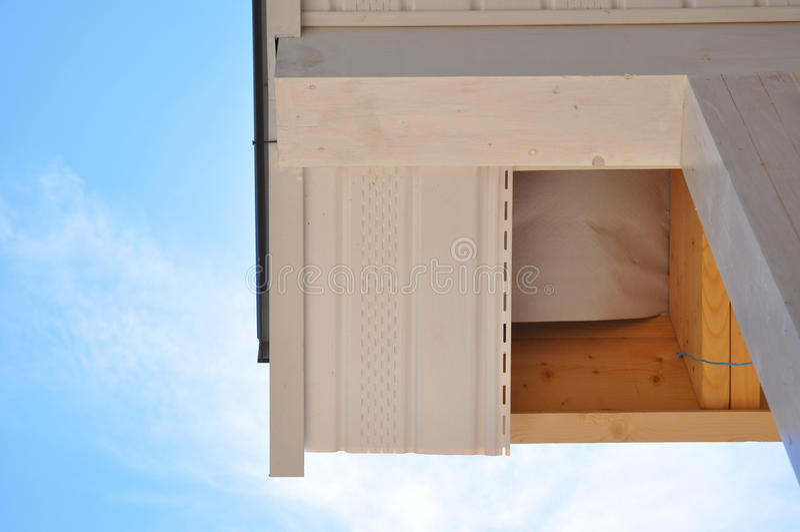Esquina de la casa con los aleros contra fondo del verano imágenes de archivo libres de regalías