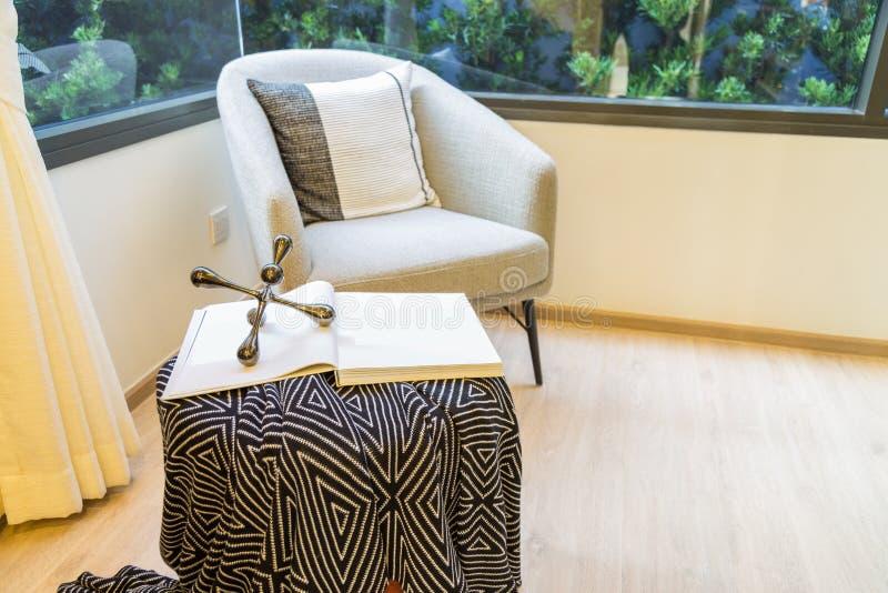 Esquina de la sala de estar con una silla del sofá y un libro en la tabla fotos de archivo libres de regalías