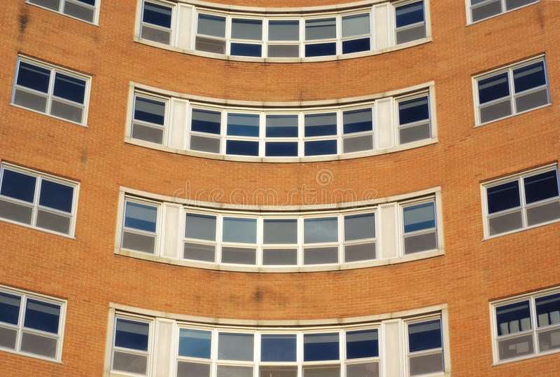 Esquina de las ventanas del edificio de ladrillo, oficina u hospital redonda, pared anaranjada fotografía de archivo libre de regalías