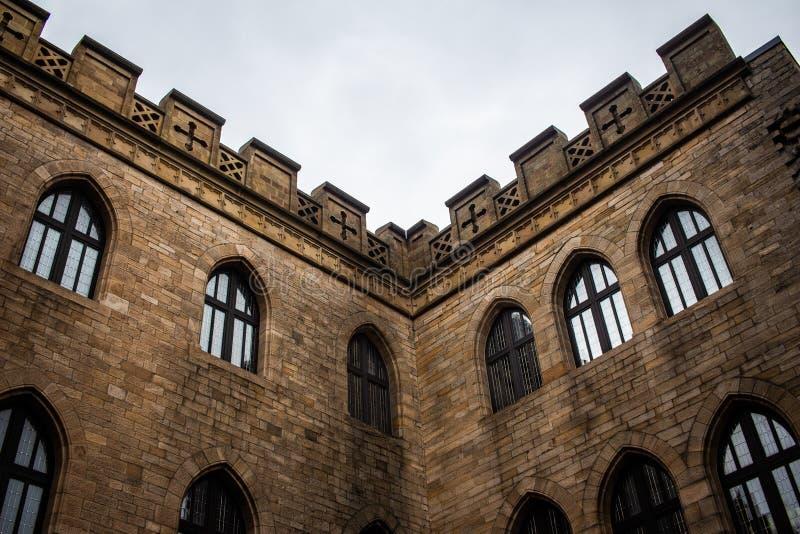 Esquina de una pared exterior vieja del castillo con Windows fotos de archivo libres de regalías