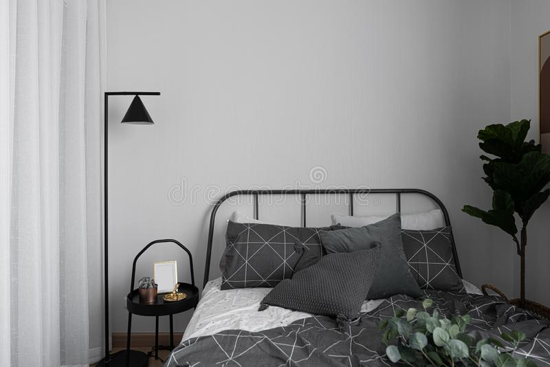 Esquina del dormitorio en estilo escandinavo con la cama gris del metal y la tabla lateral negra con la lámpara de pie mínima fotos de archivo
