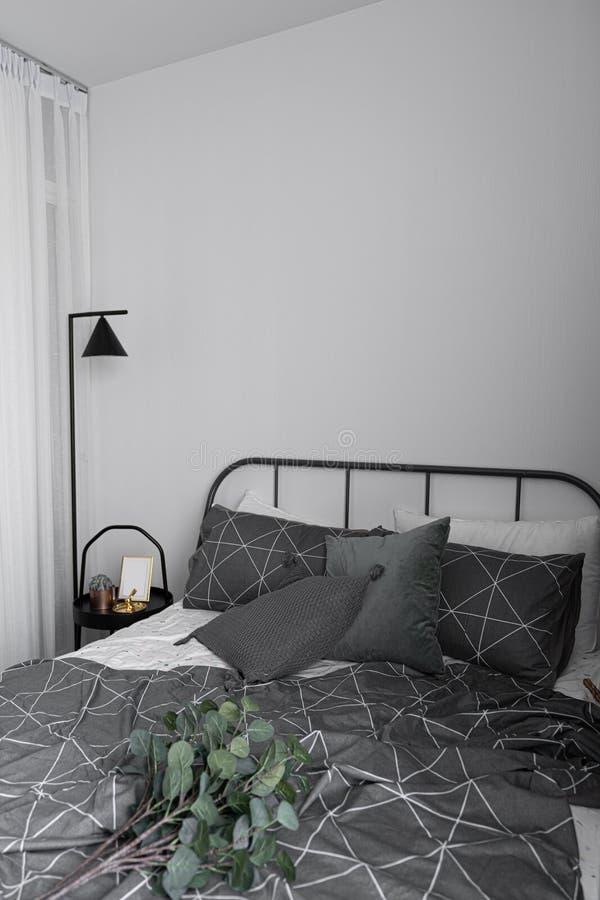 Esquina del dormitorio en estilo escandinavo con la cama gris del metal y la tabla lateral negra con la lámpara de pie mínima foto de archivo