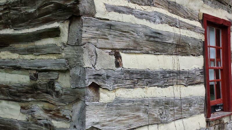 Esquina exterior y ventana de la cabaña de madera histórica foto de archivo