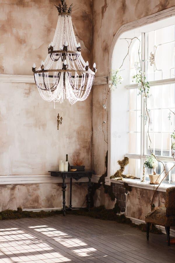 Esquina pasada de moda del sitio del vintage con la tabla y las velas negras Paredes sucias cubiertas con el helecho, luz de tech imagen de archivo