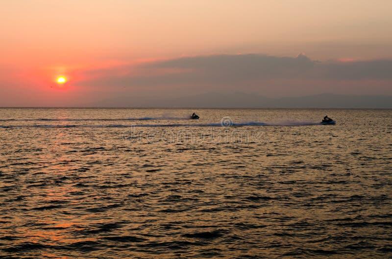 Esquis do jato no mar no por do sol fotos de stock royalty free