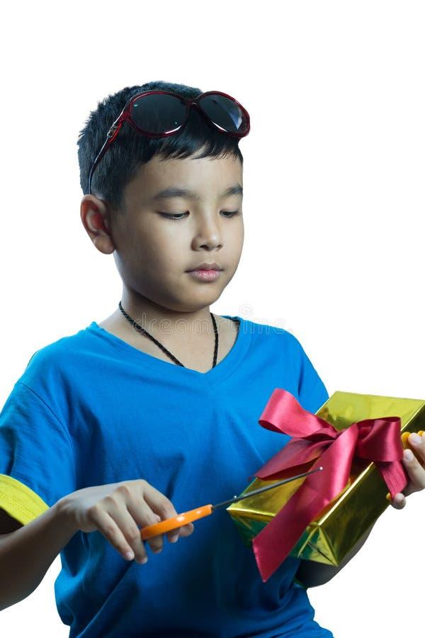 Essai asiatique d'enfant pour ouvrir son présent avec des ciseaux photos libres de droits