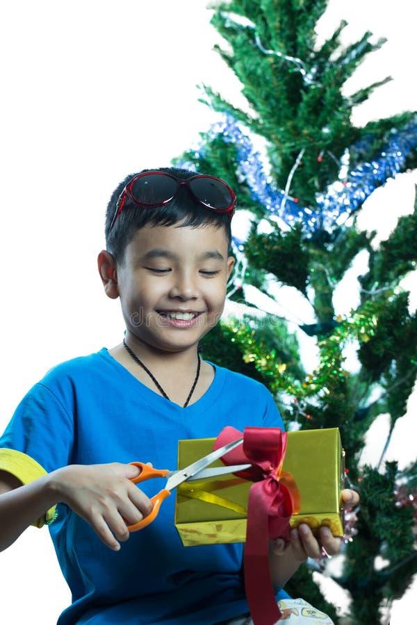 Essai asiatique d'enfant pour ouvrir son présent avec des ciseaux photos stock