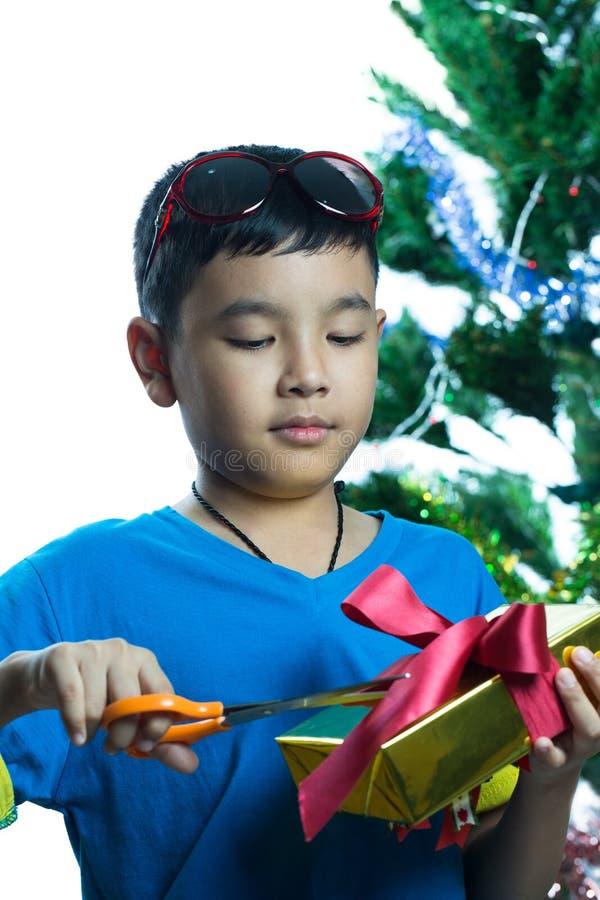 Essai asiatique d'enfant pour ouvrir son présent avec des ciseaux image stock