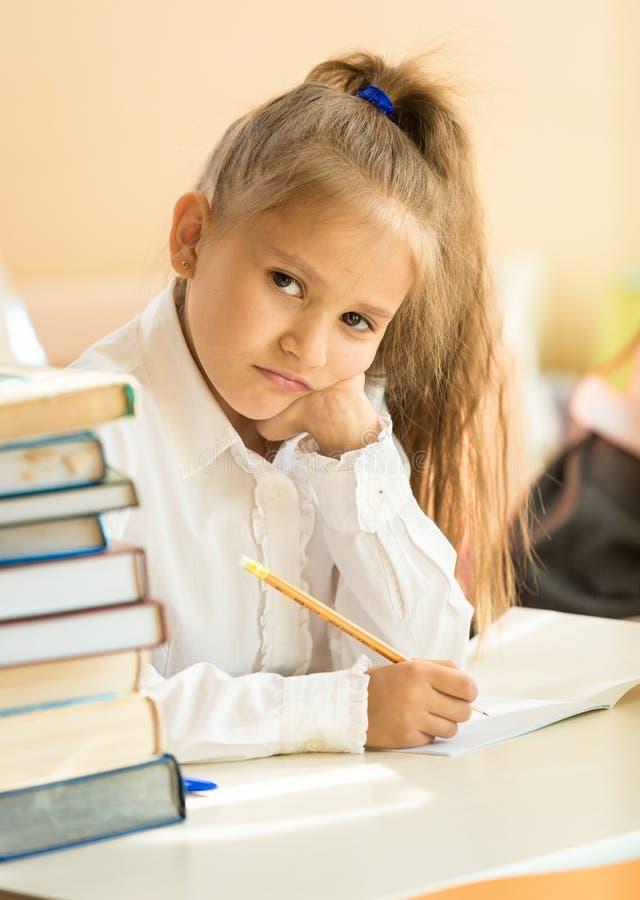 Essai bouleversé d'écriture de fille dans la salle de classe et regarder l'appareil-photo photos stock
