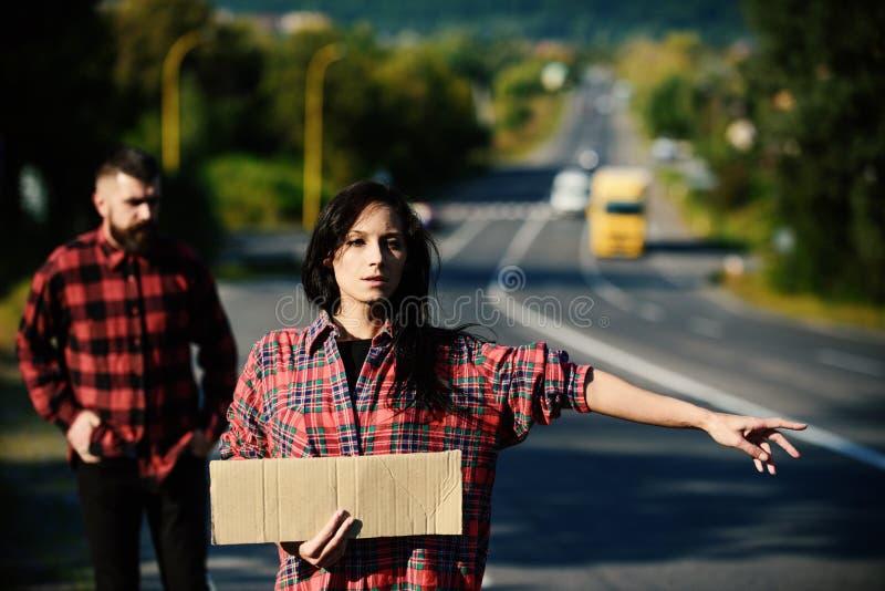 Essai de femme pour arrêter la voiture avec le signe vide de carton images libres de droits