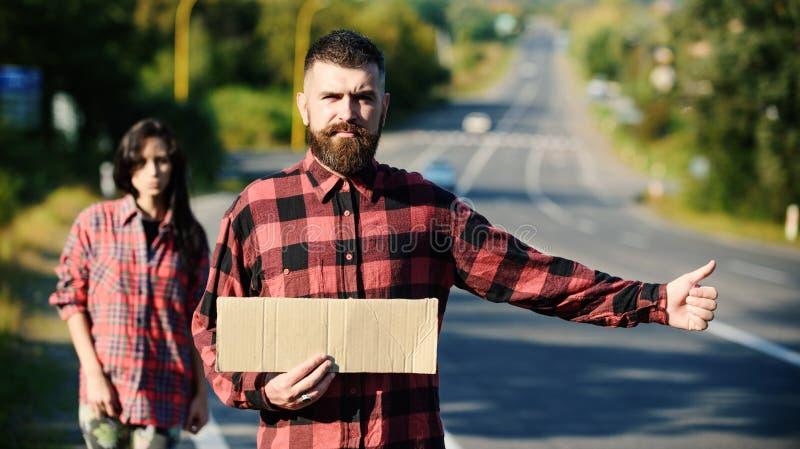 Essai de hippie pour arrêter la voiture avec le signe et le pouce de carton photographie stock libre de droits