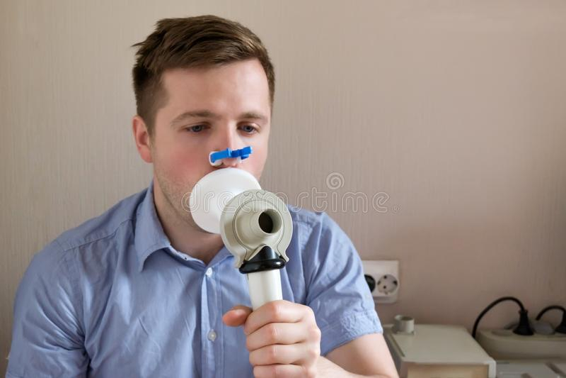 Essai de jeune homme respirant la fonction par la spirométrie photos libres de droits