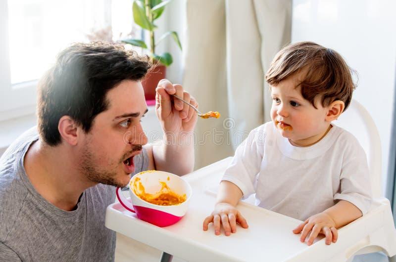 Essai de père à alimenter un garçon d'enfant en bas âge avec une cuillère dans une chaise photos libres de droits