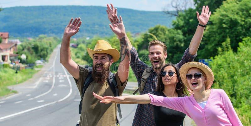 Essai de voyageurs pour arrêter la voiture Voyageurs d'amis de société faisant de l'auto-stop au fond de nature de route de bord  image stock