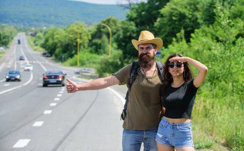 Essai de voyageurs pour arrêter la voiture L'auto-stop est l'une des manières les meilleur marché du déplacement Été de déplaceme image stock