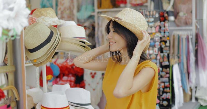 Essai modèle avec du charme sur des chapeaux dans la boutique photos libres de droits
