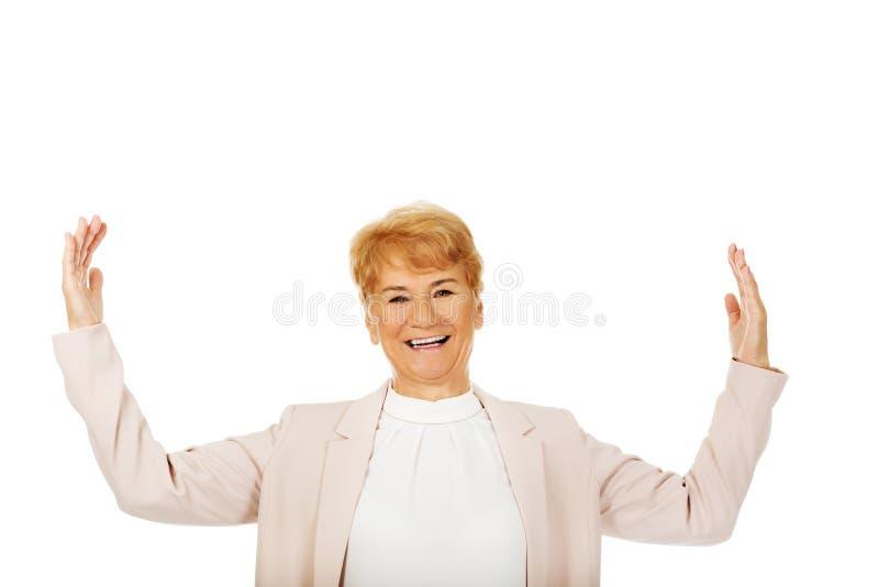 Essai plus âgé heureux de femme d'affaires pour attraper quelque chose photo stock