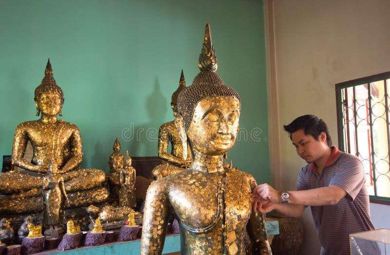 Essai thaïlandais d'homme pour raccorder un aluminium d'or à la statue de Bouddha dans le temple photos stock