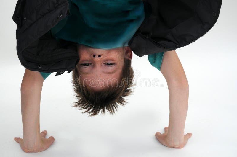 Essais de garçon pour faire un appui renversé photo libre de droits
