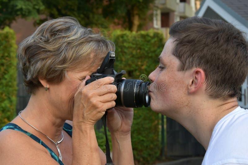Essais de mère pour prendre des photos de son fils d'adolescent photos libres de droits