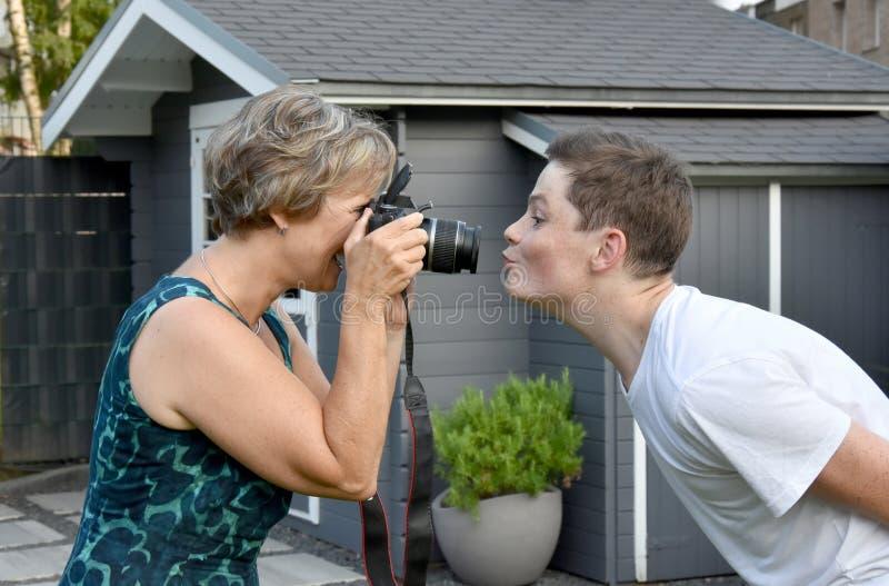 Essais de mère pour prendre des photos de son fils d'adolescent photos stock