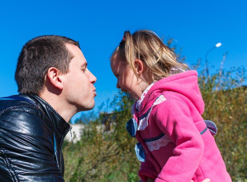 Essais de papa pour embrasser une fille Elle rit En parc dans le manteau rose image libre de droits
