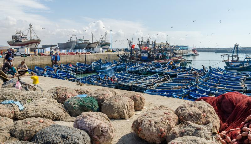 Essaouira, Marokko - 15. September 2013: Blaue hölzerne Fischerboote verankert im historischen Hafen mit Seemöwen und Fischern stockfotografie