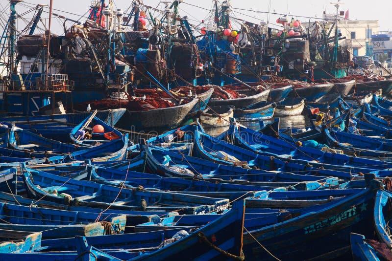 ESSAOUIRA, MARROCOS - 29 DE SETEMBRO 2011: Barcos de pesca azuis incontáveis espremidos junto em um porto totalmente abarrotado foto de stock