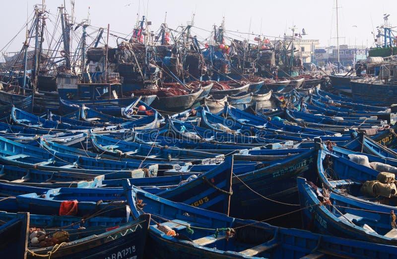 ESSAOUIRA, MARROCOS - 29 DE SETEMBRO 2011: Barcos de pesca azuis incontáveis espremidos junto em um porto totalmente abarrotado imagem de stock royalty free