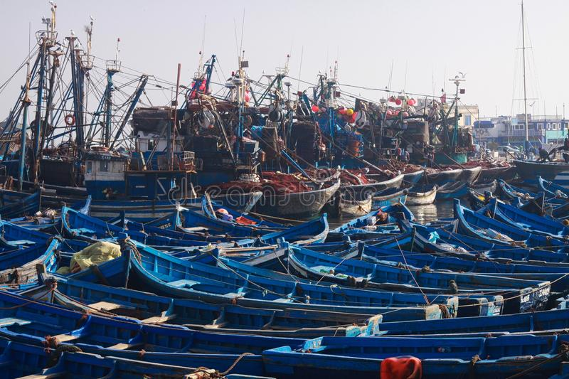 ESSAOUIRA, MOROCCO - SEPTEMBER 29. 2011: Countless blue fishing boats squeezed together in an utterly cramped harbor. Countless blue fishing boats squeezed royalty free stock photo