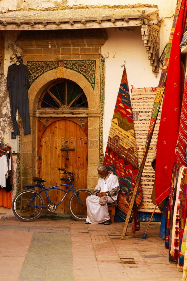 View over narrow alley on entrance of carpet rug shop with arabic man sitting in royalty free stock image