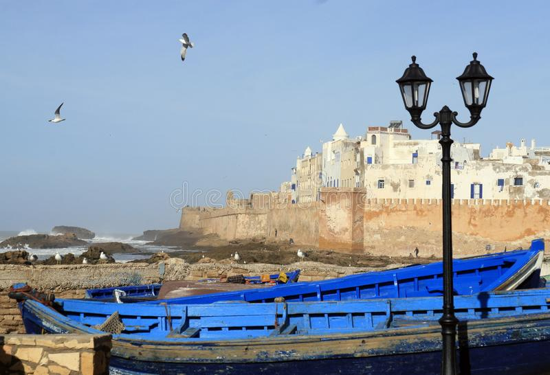 Essaouira Ramparts view with lantern and traditional blue ship in Essaouira, Morocco. Essaouira is a city in the western royalty free stock photography