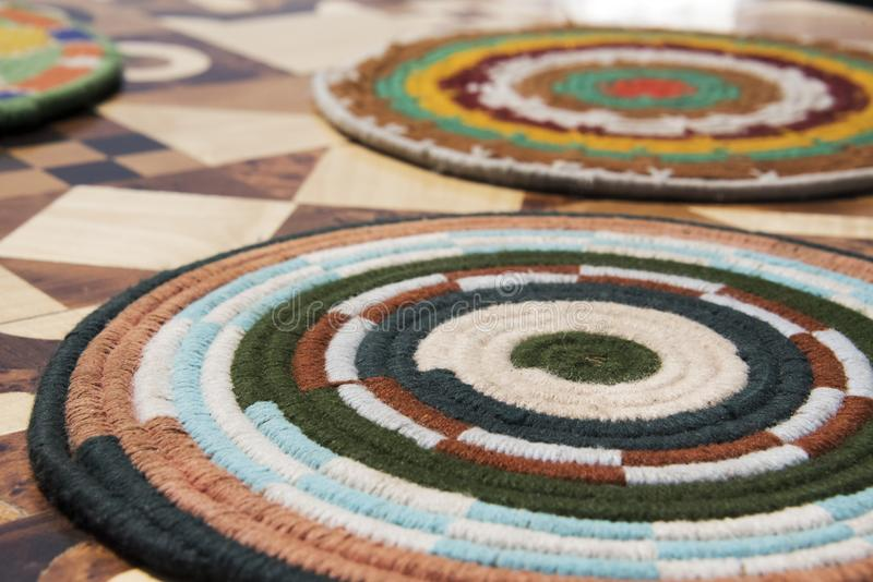 Colourful Wool table coaster on inlaid table top royalty free stock image