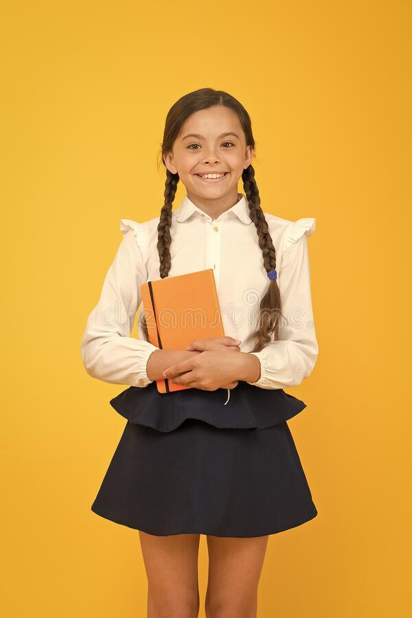 Essay for homework. KId girl student likes to study. Study literature. Private lesson. Adorable child schoolgirl hold stock photography