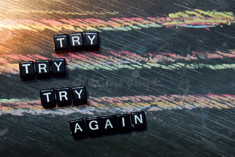 Essayez l'essai essayent encore sur les blocs en bois Image traitée croisée avec le fond de tableau noir images stock