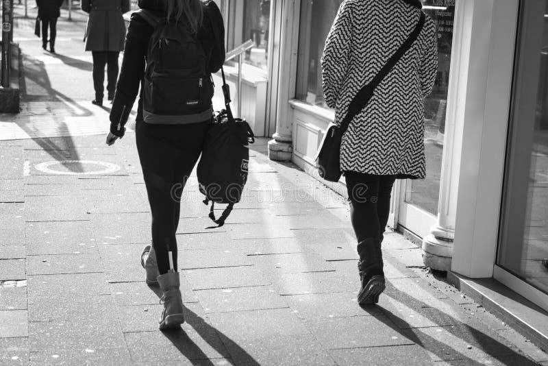 ESSEN, ALEMANIA - 25 DE ENERO DE 2017: Dos señoras unidentifed acometen a lo largo del Ruettenscheider Strasse en sus botas del i foto de archivo libre de regalías