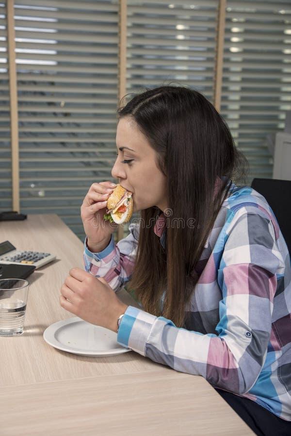 Essen beim Arbeiten im Büro lizenzfreie stockfotografie